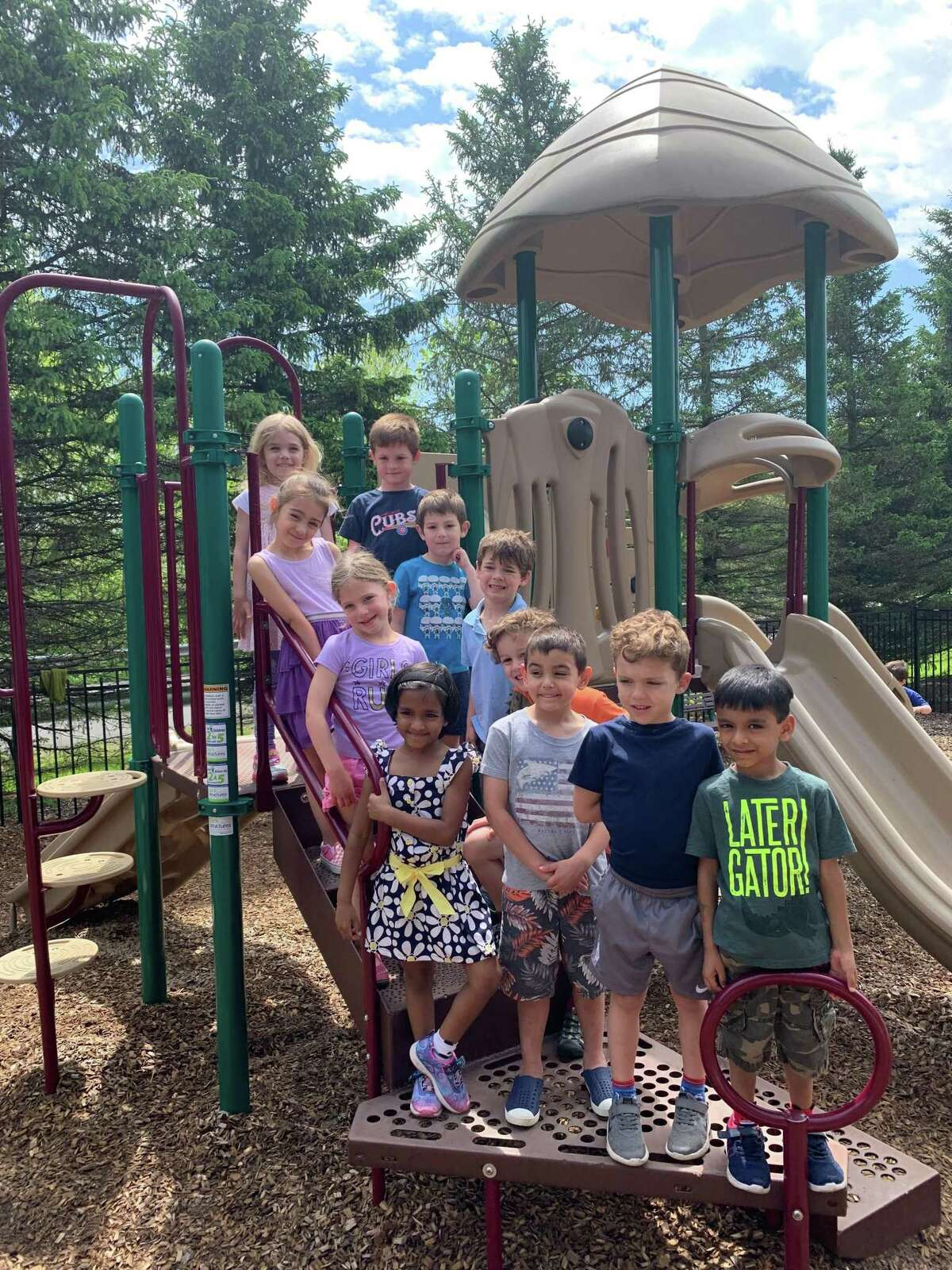 Ridgefield Montessori School students break from recess and pose for a class picture on the jungle gym.