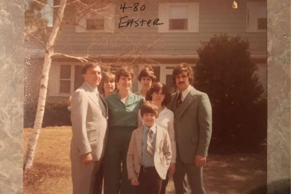 Rev. Francis P. Melfe, who left the priesthood the year before, poses with Edith Thomas and their five children, including his biological son, in Easter 1980 in front of their Debutante Manor house in Guilderland.