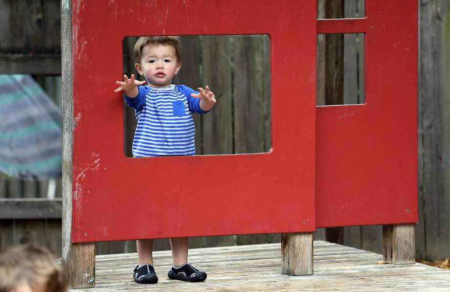Vincent Seeborn, then 2, reaches out from a structure on the playground at the Wallingford Child Care Center in Seattle. Photo: Elaine Thompson / Associated Press 2018