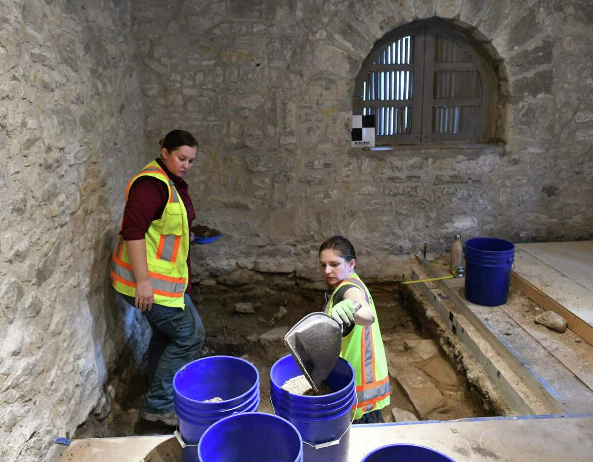 Tiffany Lindley, left, and Tyler Brown remove soil for an archaeological dig in the Long Barrack on the Alamo grounds on Tuesday, Aug. 13, 2019.