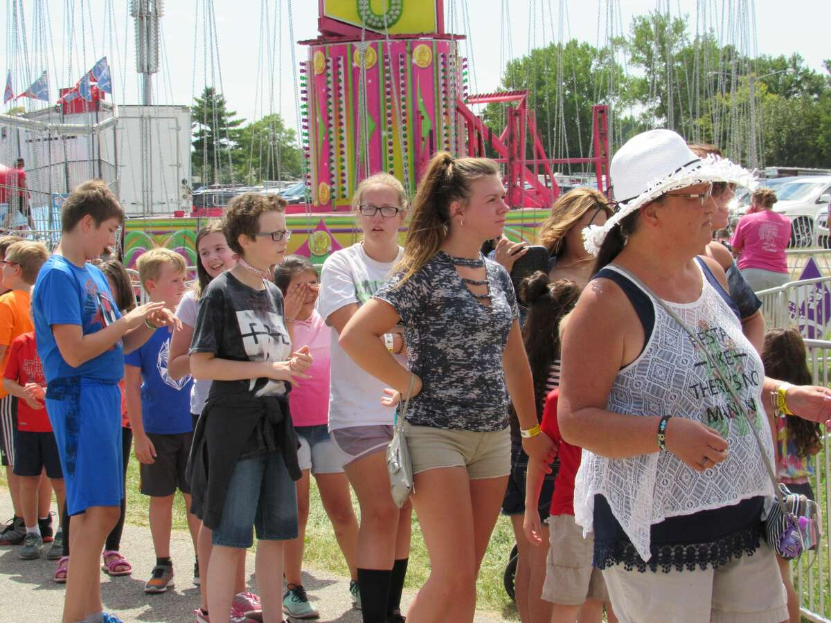 Visitors enjoy the attractions, rides and food that the Midland County Fair has to offer on Tuesday, Aug. 13, 2019.