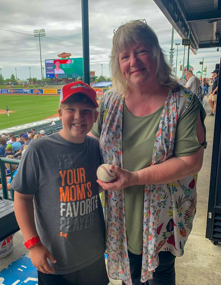 Lori Ford of Mount Morris and Landon Babcock of Coleman pose together after Babcock returned the grand slam home run ball which won Ford $5,000 during the Great Lakes Loons' Grand Slam Inning promotion on Sunday. Photo: Great Lakes Loons