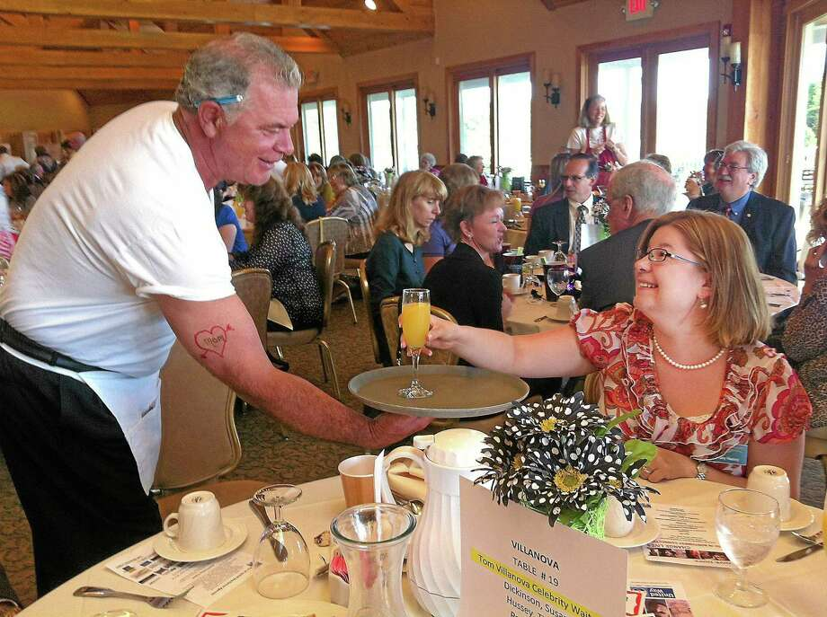 """Tom Villanova, President and CEO of Litchfield Bancorp, serves a drink to Tiffany Hussey during the United Way's annual campaign kickoff breakfast. Villanova and other business and community leaders served as """"celebrity waiters"""" during the breakfast in 2012. This year's breakfast will be held Sept. 5 at the Torrington Country Club. Photo: File Photo / Hearst Connecticut Media"""
