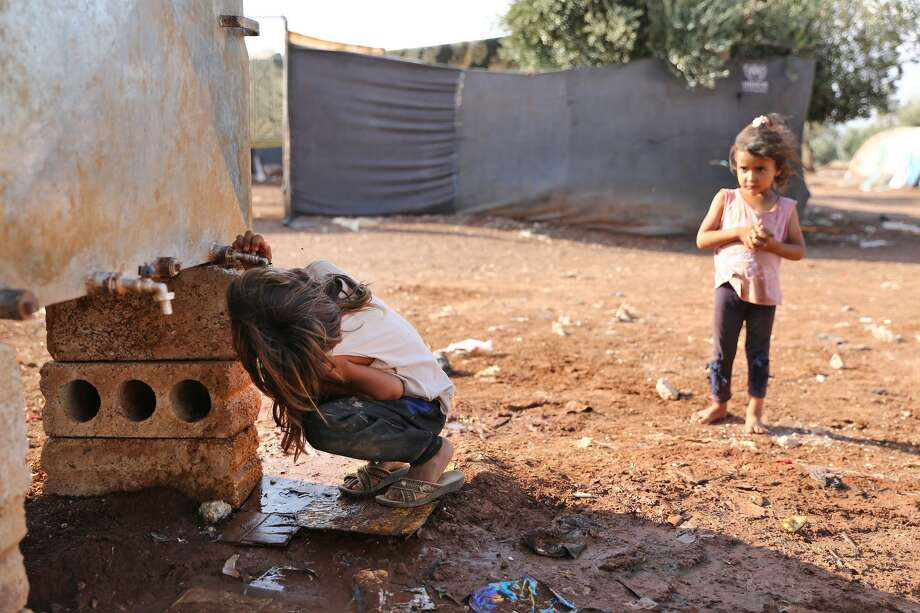A girl drinks water straight from the tap of a cistern at a camp for displaced Syrians near the village of Shamarin, near the border with Turkey in the northern Syrian Aleppo province, on August 5, 2019. (Photo by Nazeer Al-khatib / AFP)        (Photo credit should read NAZEER AL-KHATIB/AFP/Getty Images) Photo: NAZEER AL-KHATIB/AFP/Getty Images