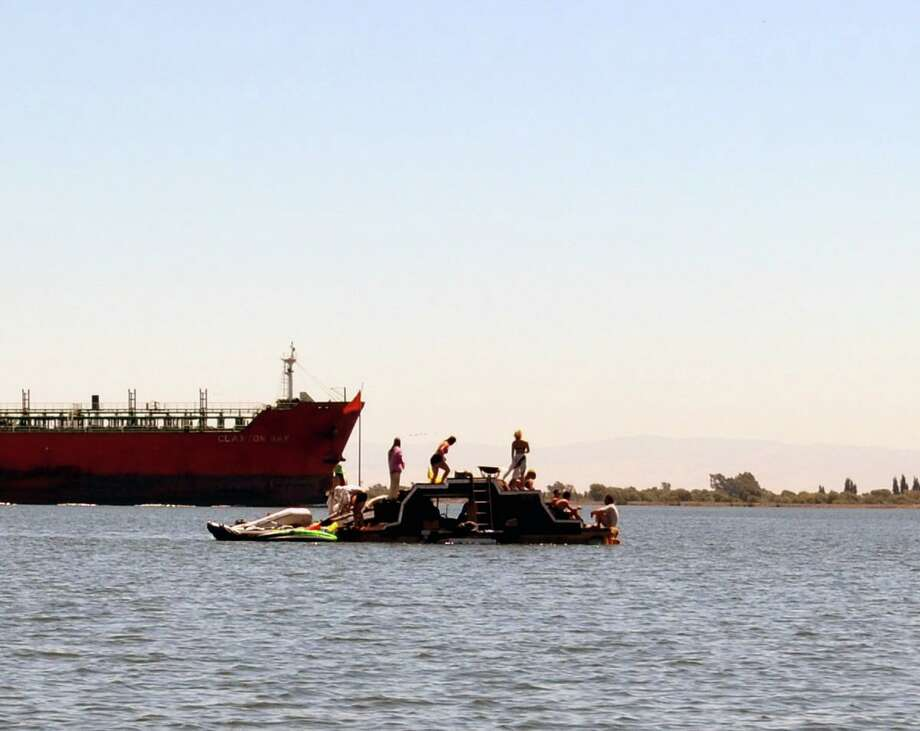 People build Siren Island at Ephemerisle in the Sacramento-San Joaquin River Delta while a cargo ship passes in the background. Photo: Gregory Thomas / The Chronicle / SFC