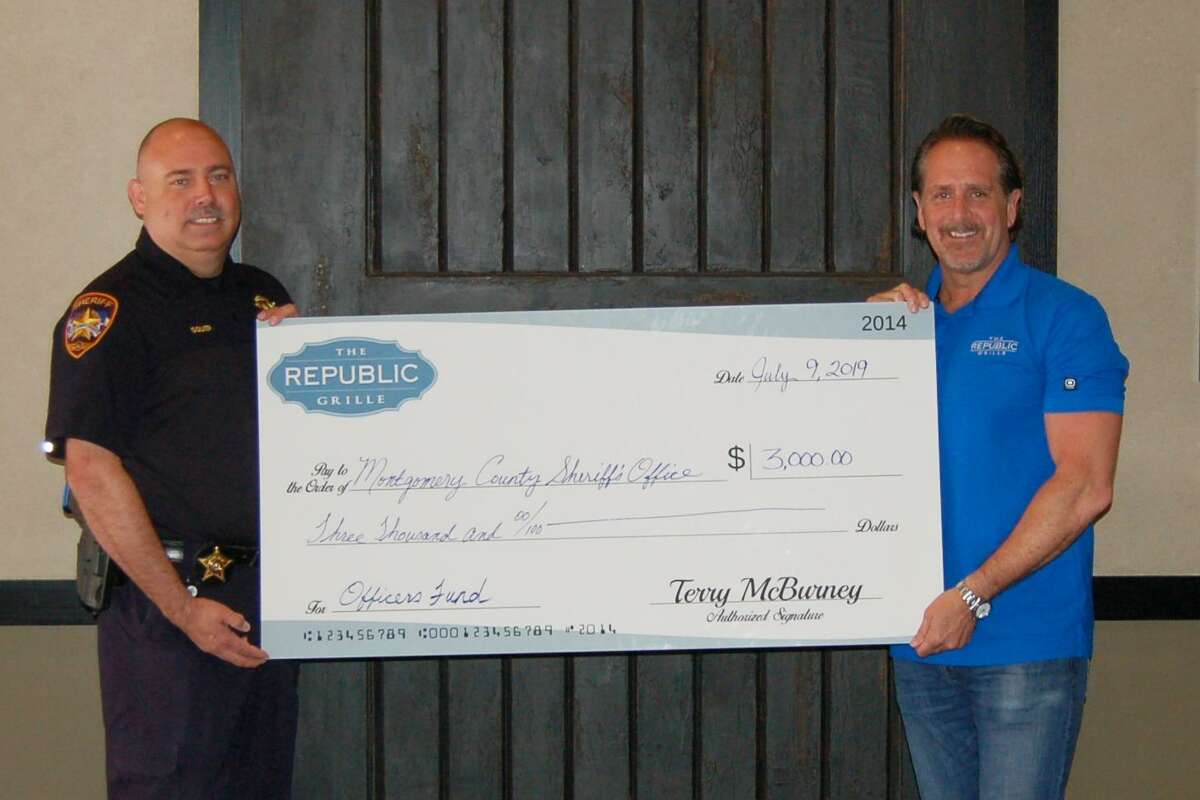 On the heels of the fifth anniversary of The Republic Grille's original location in The Woodlands Panther Creek Shopping Center, co-owners Terry and Jennifer McBurney donated $6,000 to local first responder charities. During a week-long celebration in May, a portion of lunch and dinner proceeds were designated to be given to The Woodlands Fire Department and the Montgomery County Sheriff's Office. Here, Terry McBurney presents a $3,000 check to Steve Squier of the Montgomery County Sheriff's Office Officers Fund.