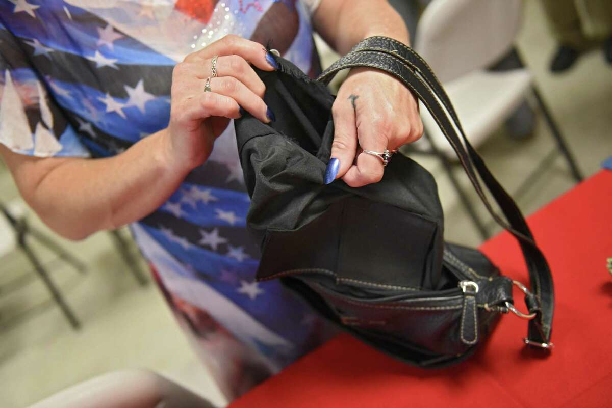 Tammie Mohan of Halfmoon shows the purse where she found the Purple Heart of WWII hero Private First Class Floyd Mabb during a ceremony with family at the American Legion Post 234 on Tuesday, Aug. 13, 2019 in Ballston Spa, N.Y. The medal was delivered to Saratoga County Clerk Craig Hayner after she found it in the lining of the purse purchased at a local garage sale. (Lori Van Buren/Times Union)