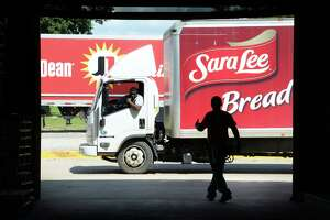 An employee helps guide a Sara Lee delivery truck into the loading bay at the Southeast Texas Food Bank on Tuesday. The delivery is part of a 15,000 pound donation of food made by Bimbo Bread, Walmart and Tyson. Photo taken Tuesday, 8/13/19