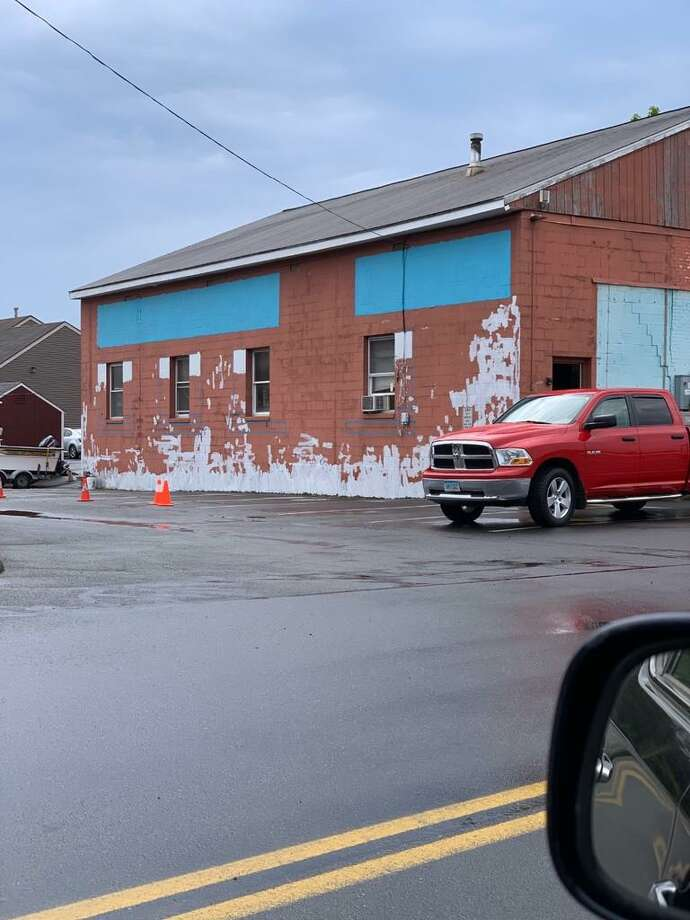 Work is under way to paint a mural on an exterior wall in the former Pierson Coal Building Photo: Contributed