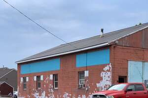 Work is under way to paint a mural on an exterior wall in the former Pierson Coal Building