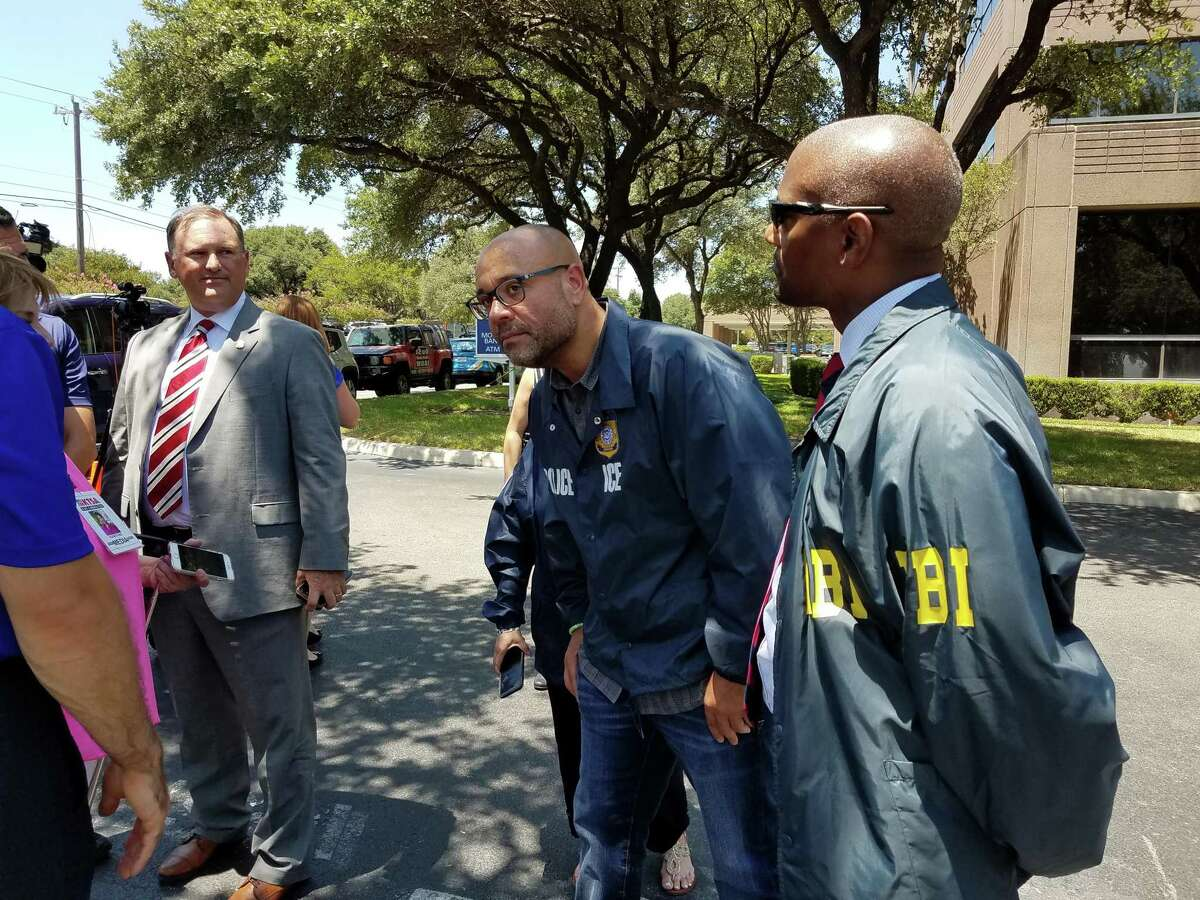 FBI agents examine one of the scenes where someone fired shots at two buildings in San Antonio that house offices connected to U.S. Immigration and Customs Enforcement.