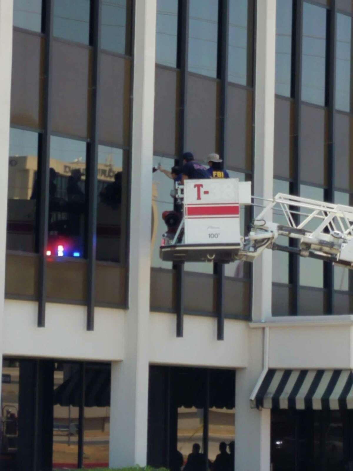 San Antonio firefighters use a ladder truck so FBI agents can examine where shots hit a building in the 1800 block of Northeast Loop 410 that houses an ICE contractor.