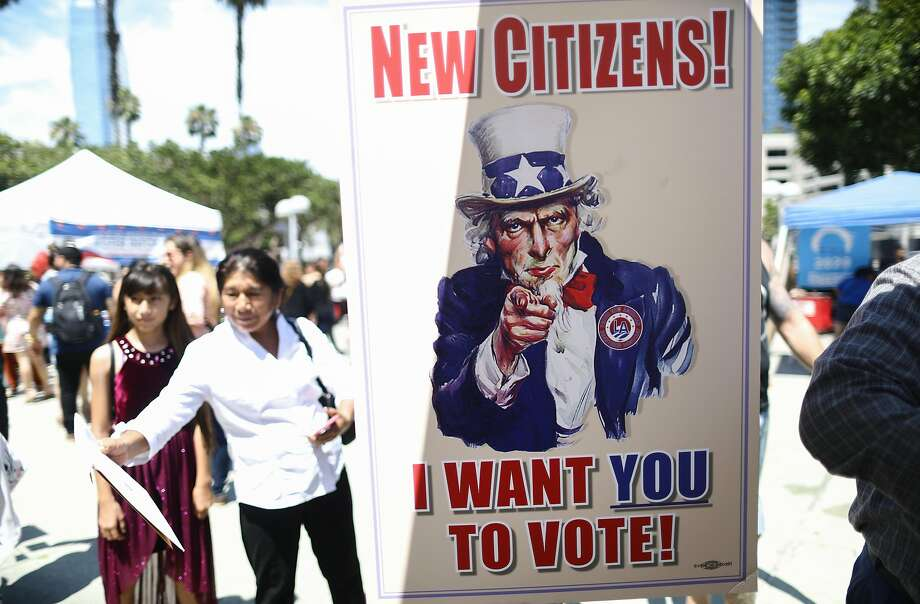 A sign is posted at a voter registration booth outside a naturalization ceremony at the Los Angeles Convention Center on July 23. Photo: Mario Tama / Getty Images
