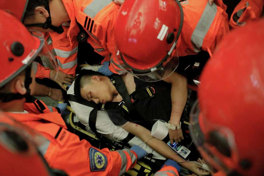 Medical staffs carry a detained man, who protesters claimed was a police officer from mainland China, during a demonstration at the Airport in Hong Kong, Tuesday, Aug. 13, 2019. Riot police clashed with pro-democracy protesters at Hong Kong's airport late Tuesday night, a chaotic end to a second day of demonstrations that caused mass flight cancellations at the Chinese city's busy transport hub. (AP Photo/Vincent Yu) Photo: Vincent Yu / Copyright 2018 The Associated Press. All rights reserved