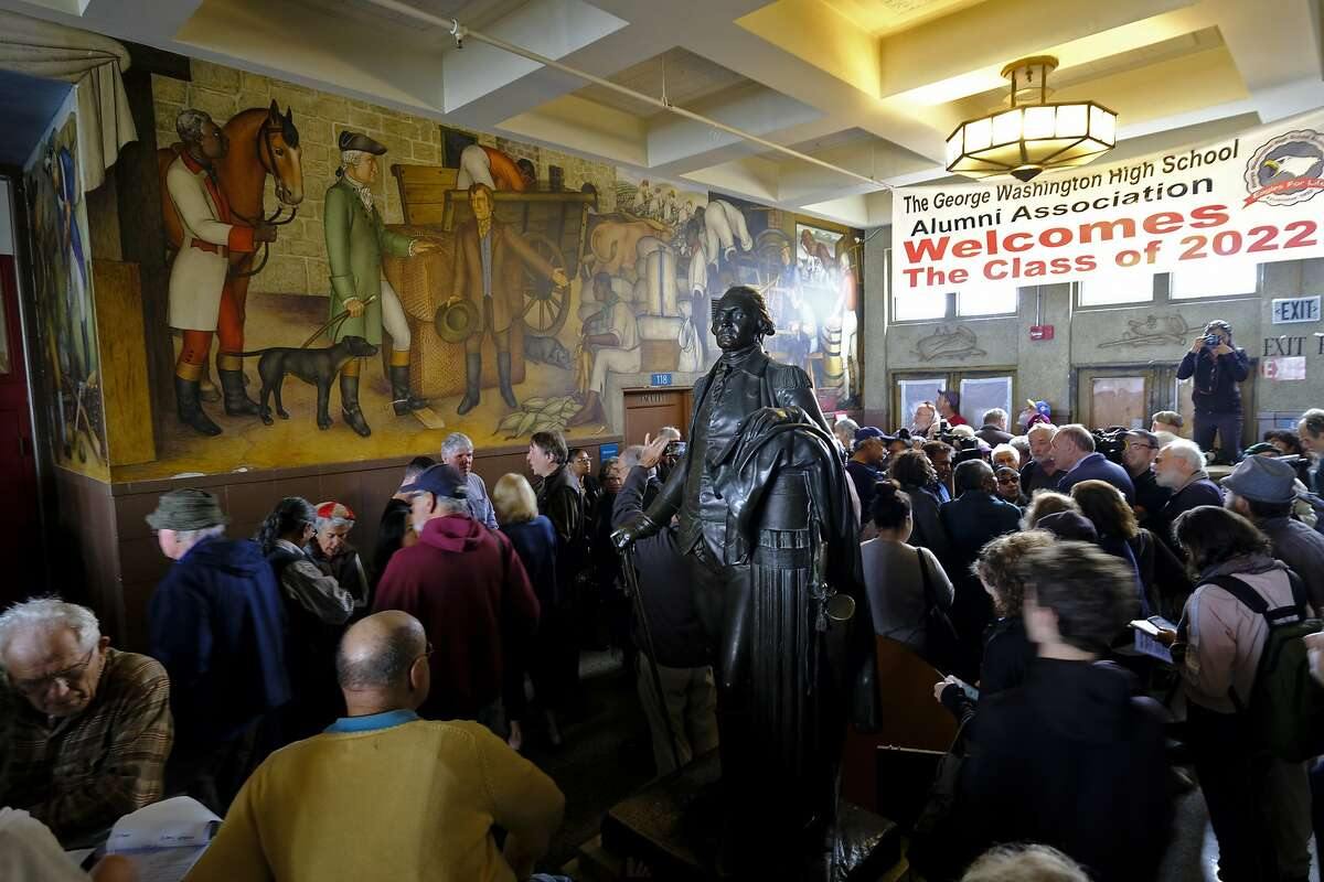 """FILE - In this Aug. 1, 2019, file photo, people fill the main entryway of George Washington High School to view the controversial 13-panel, 1,600-square foot mural, the """"Life of Washington,"""" during an open house for the public in San Francisco. San Francisco Unified School District Board of Education President Stevon Cook says he plans to introduce a solution at the school board meeting Tuesday, Aug. 13, 2019, to cover the """"Life of Washington"""" mural without destroying it. Cook says he will propose covering the mural with panels that contain artwork that shows """"the heroism of people of color in America, how we have fought against, and continue to battle discrimination, racism, hatred, and poverty."""" (AP Photo/Eric Risberg, File)"""