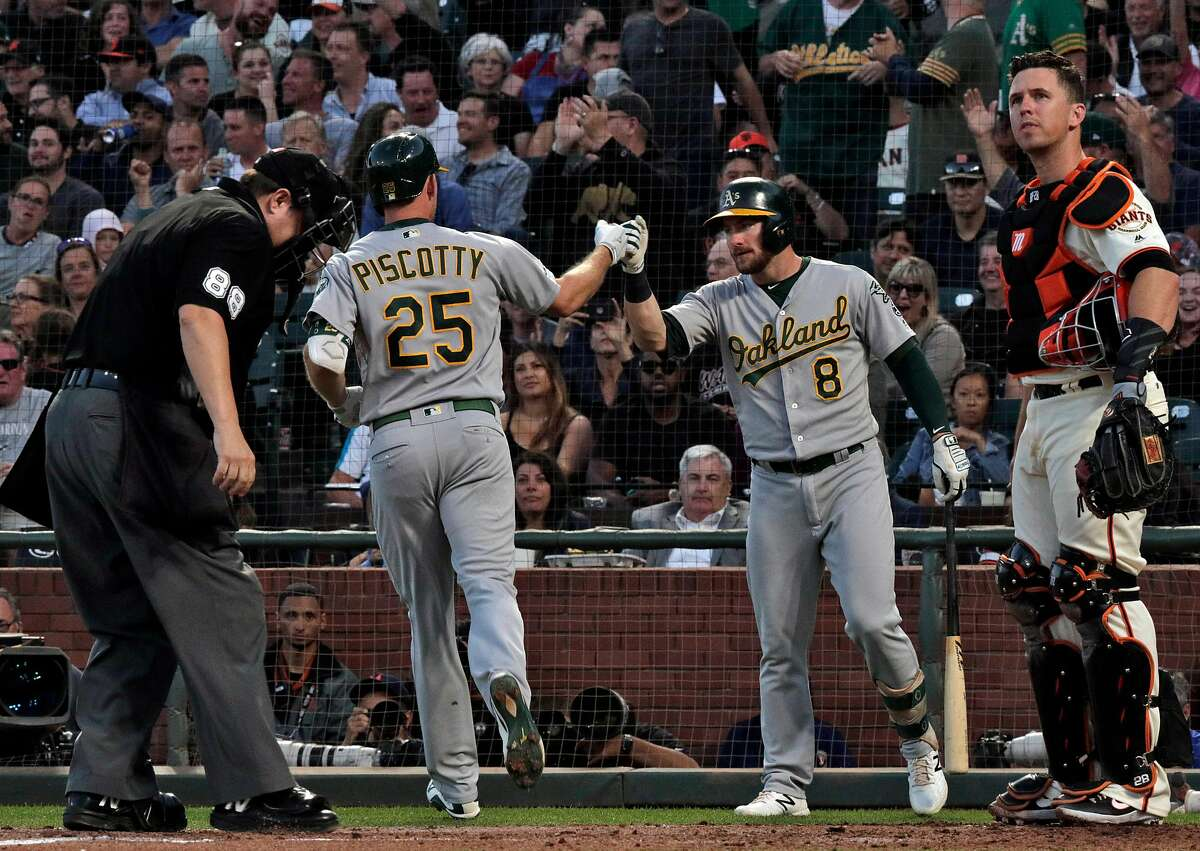 Stephen PIscotty (25) is high fived by Robbie Grossman (8) after he hit a homerun in the fifth inning as the San Francisco Giants played the Oakland Athletics at Oracle Park in San Francisco, Calif., on Tuesday, August 13, 2019.