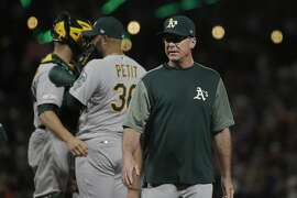 Oakland Athletics manager Bob Melvin, right, walks to the dugout after making a pitching change during the seventh inning of a baseball game against the San Francisco Giants in San Francisco, Tuesday, Aug. 13, 2019. (AP Photo/Jeff Chiu)