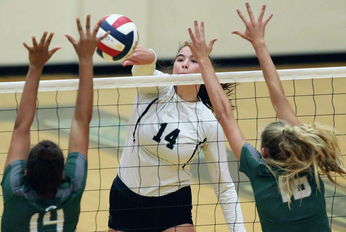 Cougar hitter Elise McGhee works a sideways shot over Rattler defenders as Reagan hosts Clark in volleyball at Littleton Gym on August 13, 2019.