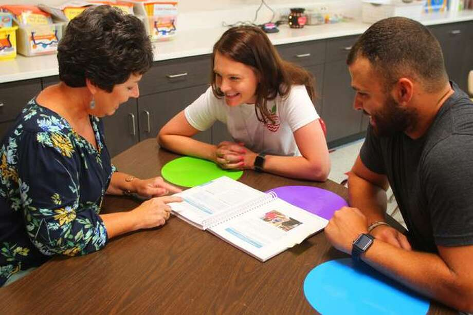 Vicky Tabeek (left) works Tuesday with teachers Samantha Gregory and Drew Comstock to develop reading and writing programs prior to the start of the school year.