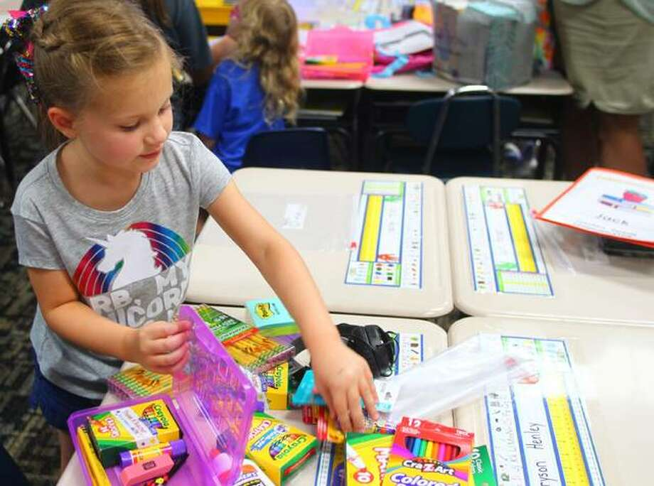 Alaina Freeman, 6, the daughter of Jacob and Kaila Freeman prepares her desk Tuesday at Murrayville-Woodson Elementary School during its Back-to-School night. Photo: Samantha McDaniel-Ogletree | Journal-Courier