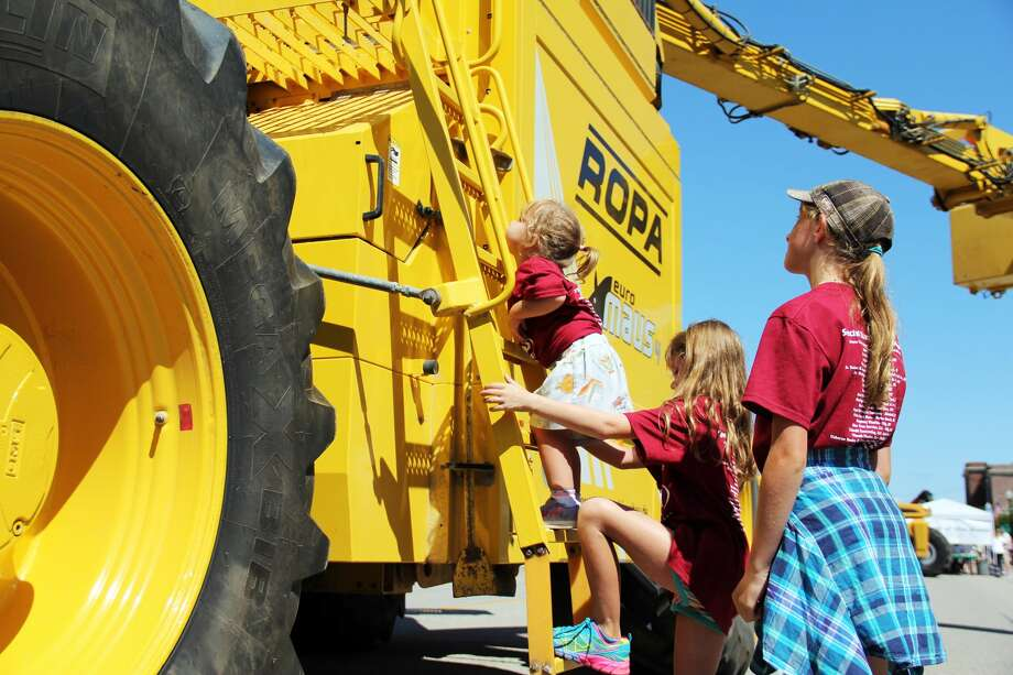 AG Venture Day was an afternoon allowing residents of all ages — including these three kiddos — to get in touch with local agricultural heritage. The Harbor Beach-based event had several tractors and combines available for viewing. Photo: Andrew Mullin/Huron Daily Tribune