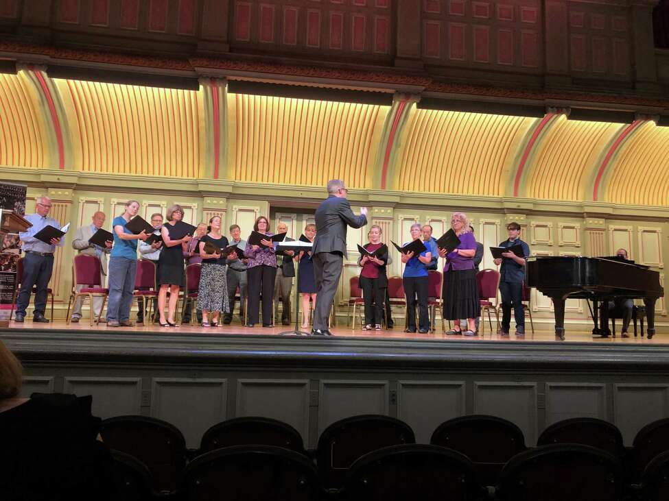 Jose Daniel Flores-Caraballo conducting Albany Pro Musica singers at a Troy Music Hall event announcing gifts to the ensemble (photo courtesy Overit Media / Albany Pro Musica)