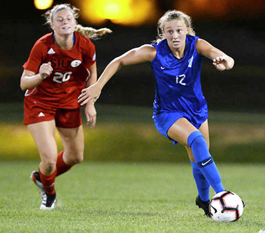 Brianna Halverson pf Saint Louis University (12) moves the ball past SIUE's Courtney Benning in exhibition action Tuesday night at Saint Louis U's Hermann Stadium. The Billikens beat SIUE 2-0. Photo: SLU Athletics
