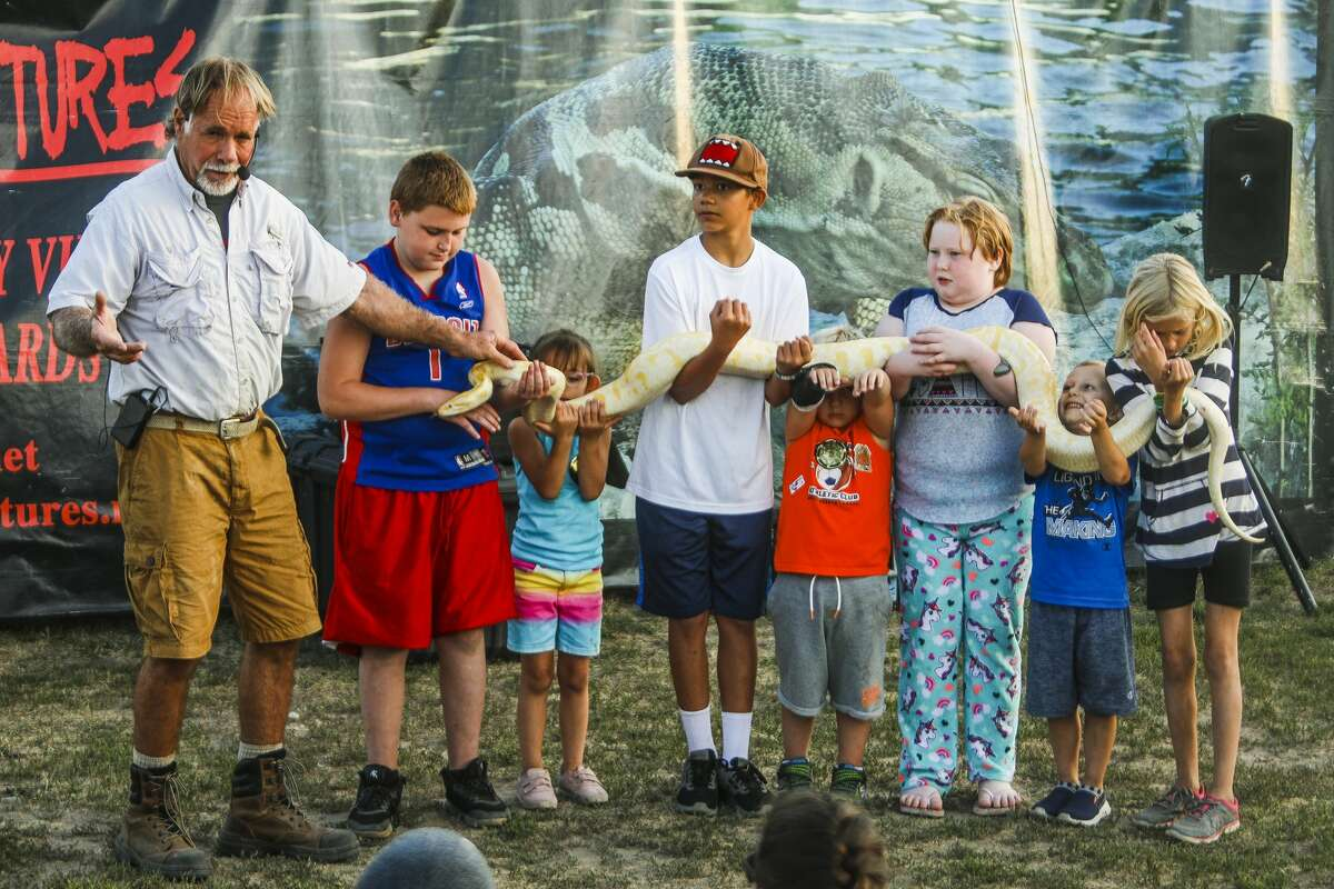Danny Conner, left, provides the audience with facts about an 8-year-old Burmese python named Apollo as several children hold onto the snake during Danny Conner's Reptile Adventures show on Tuesday, Aug. 13, 2019 at the Midland County Fair. (Katy Kildee/kkildee@mdn.net)