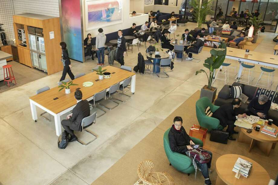 People sit workspaces at the at the offices of WeWork in Tokyo on Dec. 20, 2018. Photo: Bloomberg Photo By Keith Bedford. / © 2018 Bloomberg Finance LP