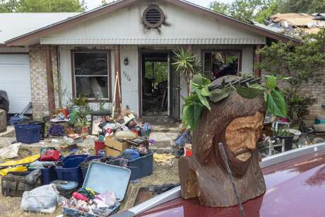 A wooden bust of Jesus recovered Tuesday, Aug. 6, 2019 from the fire-damaged home in the 7500 block of Dream Valley where an apparent triple homicide-suicide occurred sits on the roof of a car apparently undamaged by the fire. Four people from one family died in the Monday night incident.