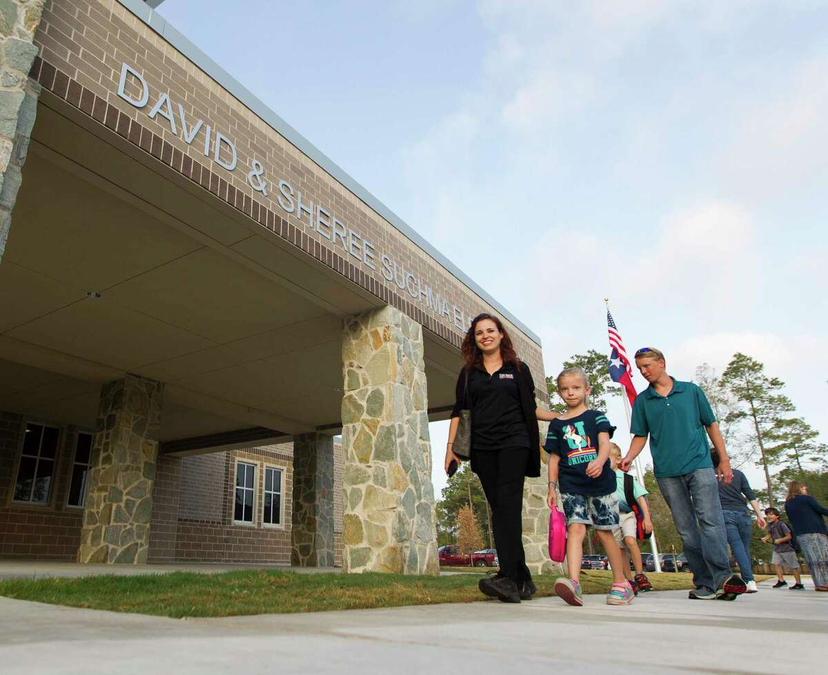 Students walk toward the newly opened Suchma Elementary on the first day of school for Conroe ISD, Wednesday, Aug. 14, 2019, in Conroe.
