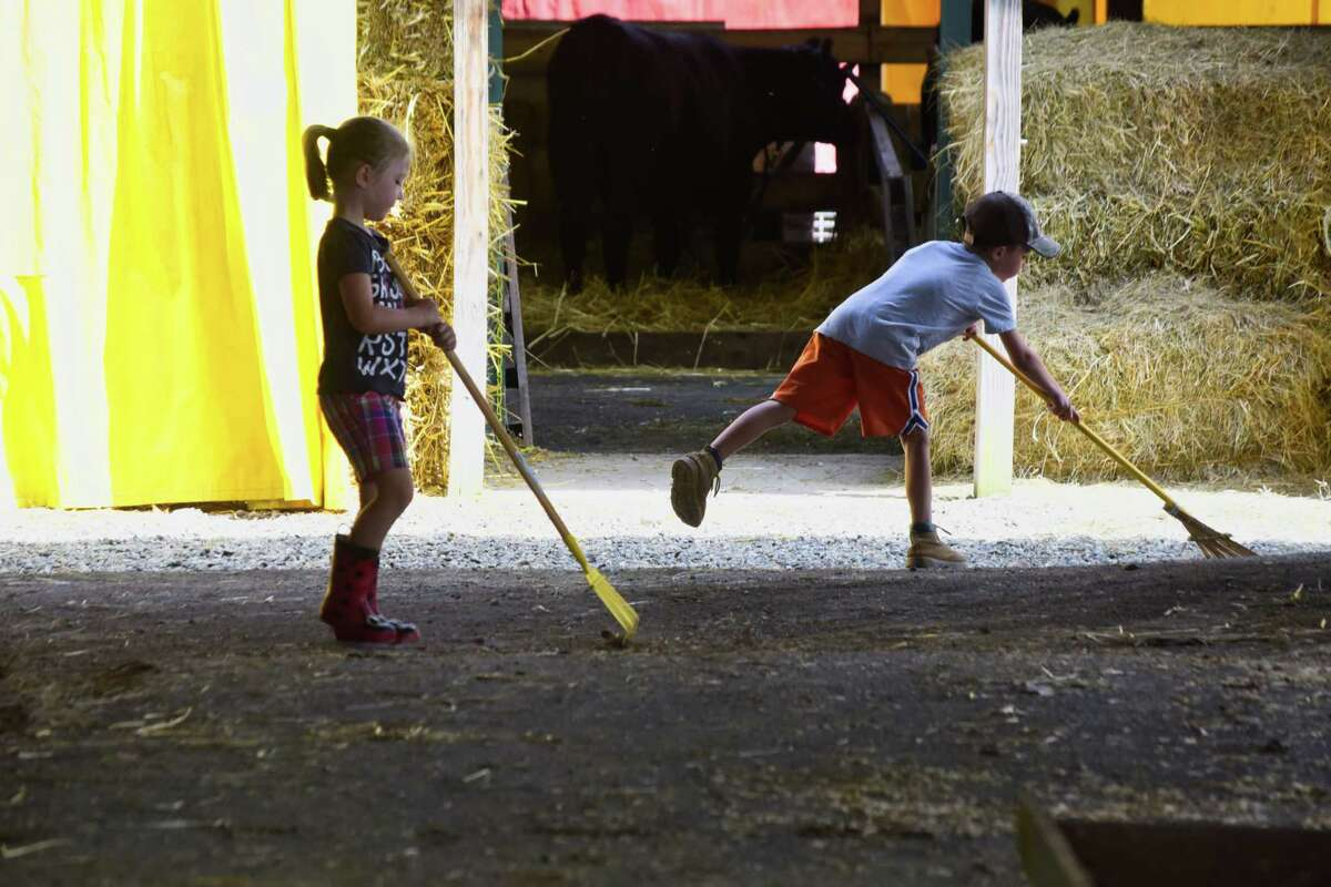 Kyla Gilchrist, 4, left, and her brother, Charlie, 6, from Shushan rake up around the stalls at the Washington County Fair on Monday, Aug. 20, 2018, in Greenwich, N.Y. Charlie will show his heifer calf on Thursday and Friday. The fair runs through Sunday, Aug. 26th. (Paul Buckowski/Times Union)