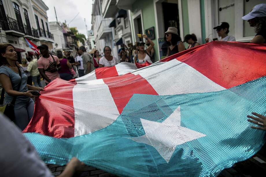 People hold the flag of Puerto Rico as they celebrate on the day Governor Ricardo Rossello resigns from office in San Juan, Puerto Rico, on Aug. 2, 2019. Photo: Bloomberg Photo By Xavier Garcia. / © 2019 Bloomberg Finance LP