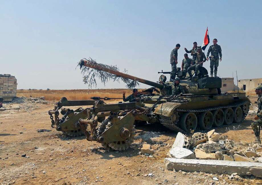 Syrian soldiers flash the victory sign after capturing several northwestern villages. Photo: Syrian Arab News Agency