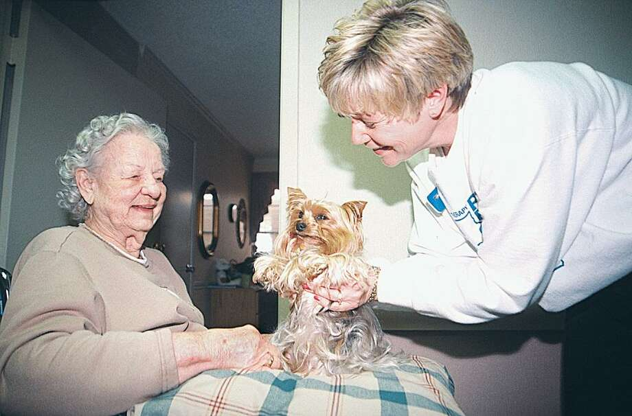 Seniors can benefit greatly from pet therapy. Here, a volunteer, right, introduces Annie, center, to a retirement home resident. Photo: Hearst Connecticut Media File Photo / Freelance