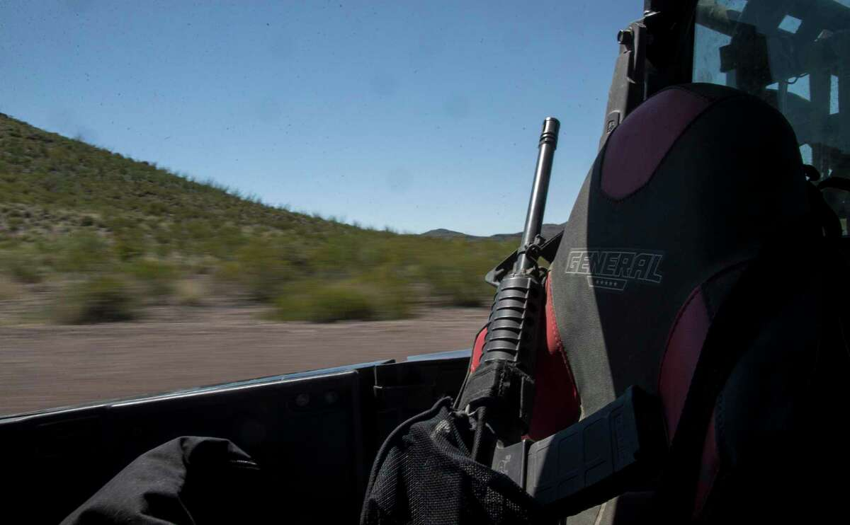 A rifle sits in the back of Thomas Allen Rawls' utility vehicle as he surveys the ranch where he works on Friday, July 26, 2019, in Presidio County. Rawls views the gun as a tool in the harsh environment.