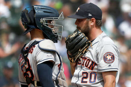 Houston Astros catcher Robinson Chirinos, left, talks with starting pitcher Wade Miley during the second inning of a baseball game against the Chicago White Sox Wednesday, Aug. 14, 2019, in Chicago. (AP Photo/Charles Rex Arbogast)