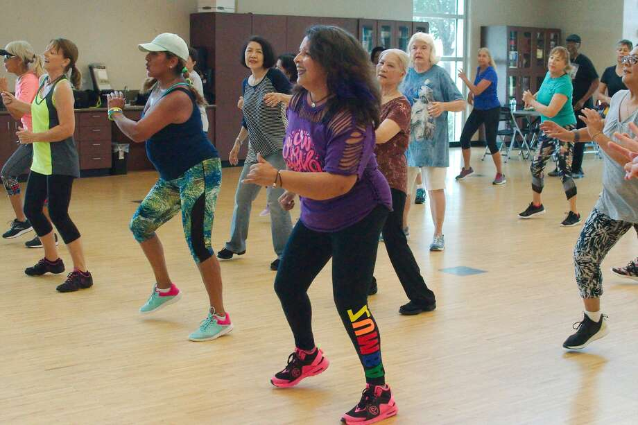 Instructor Gina Gills, center, leads the Zumba class that combines dancing and exercise Tuesday, Aug. 13 at Hometown Heroes park. Photo: Kirk Sides/Staff Photographer