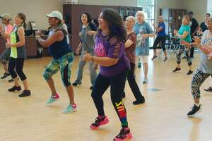 Instructor Gina Gills, center, leads the Zumba class that combines dancing and exercise Tuesday, Aug. 13 at Hometown Heroes park.