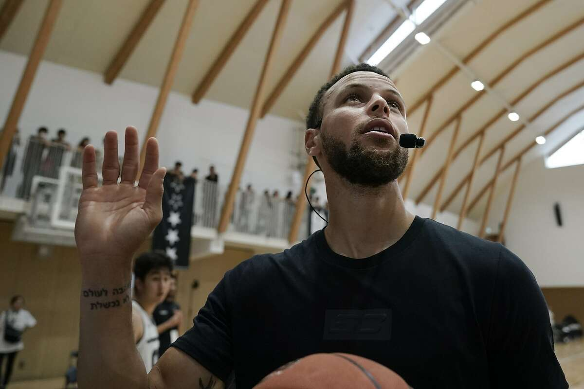 """File - In this June 23, 2019, file photo, Golden State Warriors' Stephen Curry waves toward the fans while coaching at a high school basketball camp in Tokyo. Someday, years or even decades from now, at one of those celebratory reunions teams like to do, Stephen Curry knows he and Kevin Durant will reminisce with fondness about their three insanely successful years together on the Golden State Warriors. For now, Curry is embracing """"new beginnings"""" as the oldest player on a Golden State roster that will look far different come training camp next month. (AP Photo/Jae C. Hong, File)"""