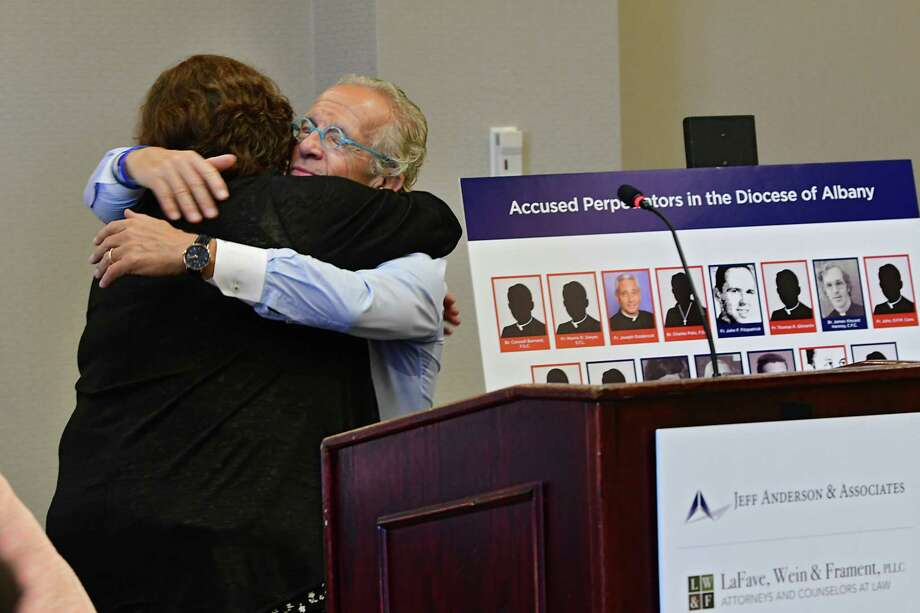 Survivor Jeanne Marron hugs attorney Jeff Anderson next to board of perpetrators in the Diocese of Albany during a press conference where Anderson announced 20 lawsuits filed against the Albany Diocese on the first day the Child Victims Act at the Hilton Albany on Wednesday, Aug. 14, 2019 in Albany, N.Y. The act allows a one-year period for claims to be filed regardless of the age of the plaintiff. Survivor and advocate Bridie Farrell stands at right. (Lori Van Buren/Times Union) Photo: Lori Van Buren, Albany Times Union / 20047654A