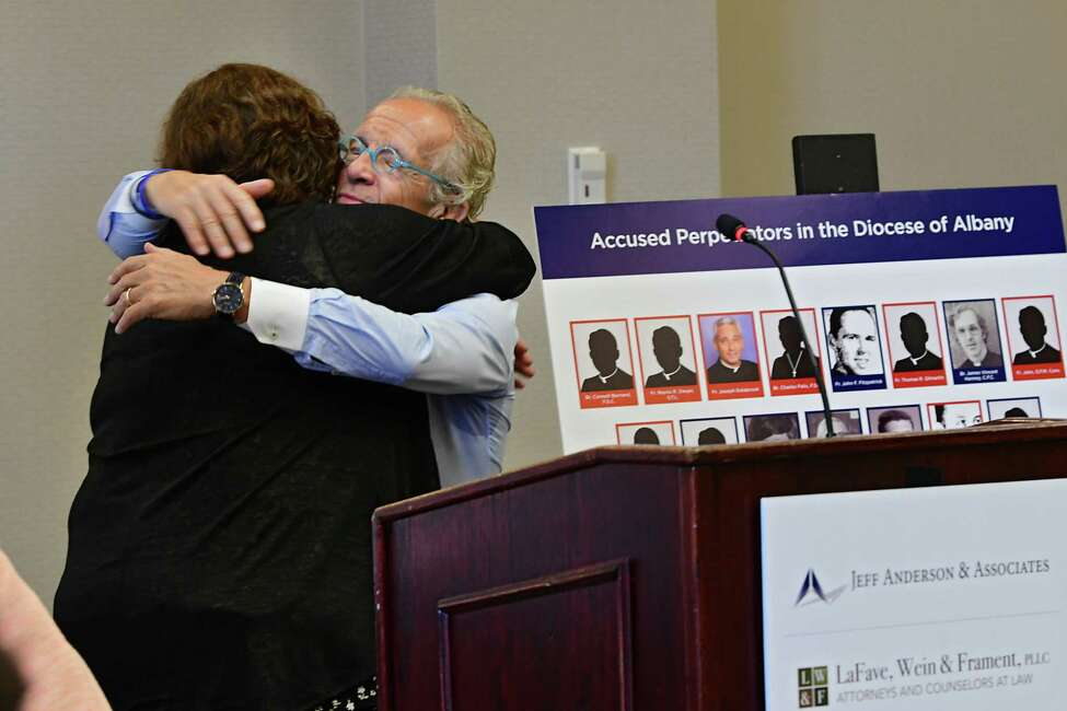 Survivor Jeanne Marron hugs attorney Jeff Anderson next to board of perpetrators in the Diocese of Albany during a press conference where Anderson announced 20 lawsuits filed against the Albany Diocese on the first day the Child Victims Act at the Hilton Albany on Wednesday, Aug. 14, 2019 in Albany, N.Y. The act allows a one-year period for claims to be filed regardless of the age of the plaintiff. Survivor and advocate Bridie Farrell stands at right. (Lori Van Buren/Times Union)