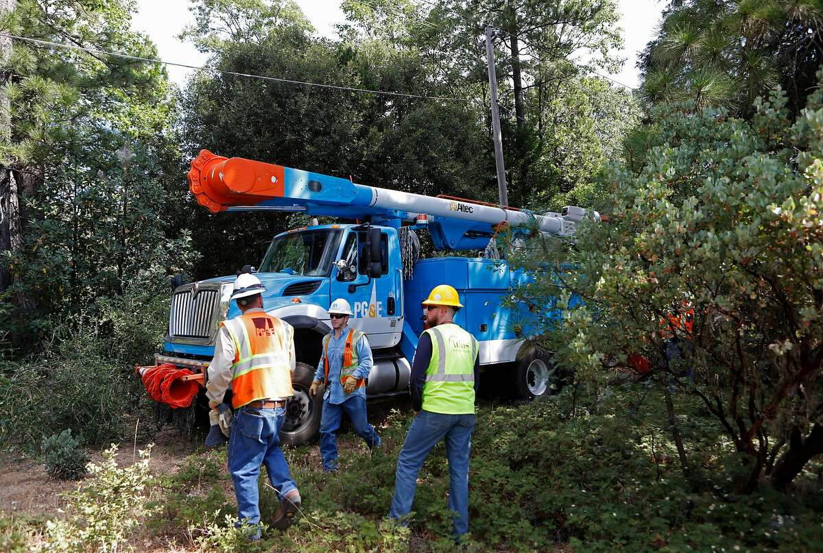 A PG&E crew navigates the thick brush to make a power line repair, as PG&E performs a public safety power shutoff drill around Foresthill, Ca. on Thurs. August 8, 2019, Helicopters and trucks, are used in a trial run for how it will inspect power lines before turning them on after a shut down.