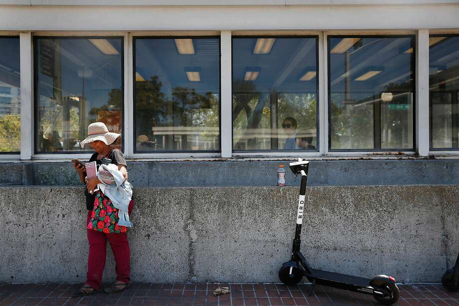 Zeida Flores of Berkeley keeps her head cool under a woven hat as she waits for her bus outside the Lake Merritt BART station on Wednesday, August 14, 2019  in Oakland, Calif. Photo: Lea Suzuki / The Chronicle