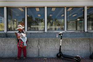 Zeida Flores of Berkeley keeps her head cool under a woven hat as she waits for her bus outside the Lake Merritt BART station on Wednesday, August 14, 2019  in Oakland, Calif.