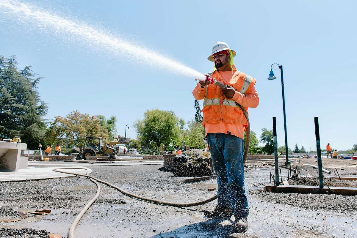 Kristian Barocio with Goodline Landscaping of Tracy sprays water on a section of gravel while working on a playground renovation in Livermore, Calif, on Wednesday, August 14, 2019. A high pressure area over the Bay area will trigger dangerous levels of summer heat and heat advisories have been issued for portions of Alameda, Contra Costa and other central valley counties.