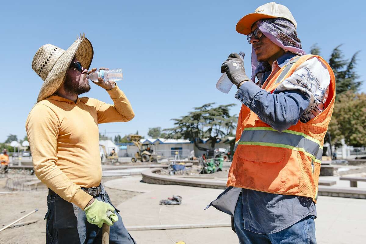 Cousins Santiago Elias, left, and Jesus Elias with Goodline Landscaping of Tracy take a water break while working on a playground renovation in Livermore, Calif, on Wednesday, August 14, 2019. A high pressure area over the Bay area will trigger dangerous levels of summer heat and heat advisories have been issued for portions of Alameda, Contra Costa and other central valley counties.