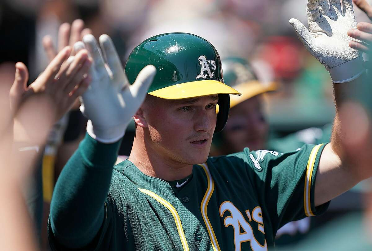 SAN FRANCISCO, CA - AUGUST 14: Matt Chapman #26 of the Oakland Athletics is congratulated by teammates after he scored against the San Francisco Giants in the top of the third inning at Oracle Park on August 14, 2019 in San Francisco, California. (Photo by Thearon W. Henderson/Getty Images)
