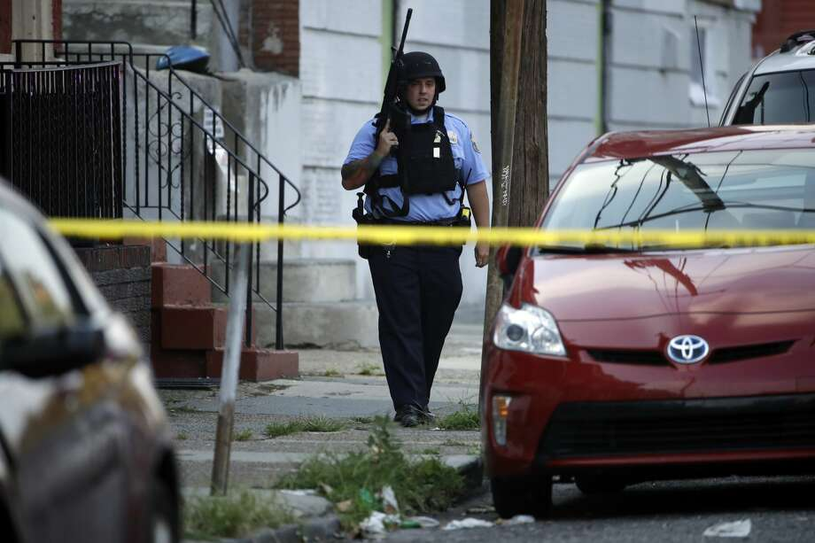 A police officer patrols the block near a house as they investigate an active shooting situation, Wednesday, Aug. 14, 2019, in the Nicetown neighborhood of Philadelphia. (AP Photo/Matt Rourke) Photo: Matt Rourke/AP
