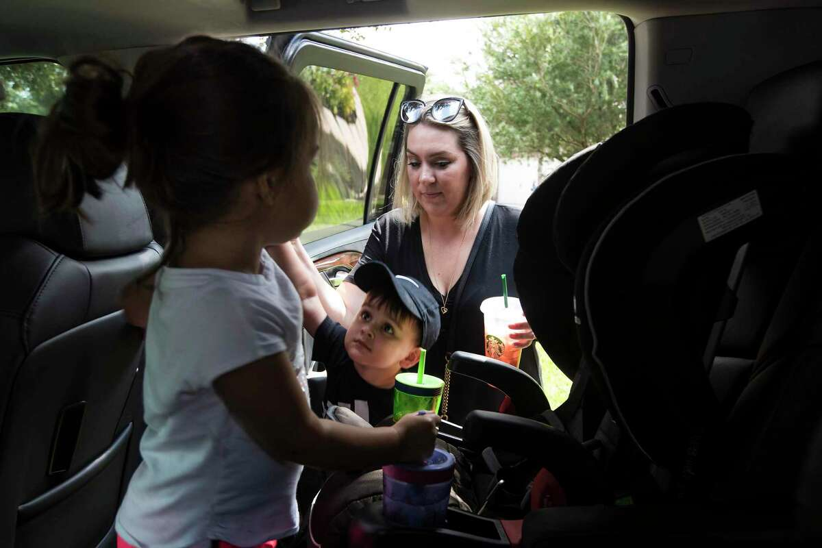 Amanda Wallace helps her 3-year-old twins Kaia and Cayden Olivarez put on their shoes as they get ready to go play at the park on Wednesday in Kingwood. She is among the Texans who have filed complaints against Aliera, a Georgia company accused of deceiving its members into buying health plans through an affiliated Christian health share ministry they thought were full coverage insurance but in the end were worthless. In April, Wallace had severe abdominal pain and went to a Kingwood hospital emergency room. She was billed $30K which Aliera refused to pay saying it was not enough of a life threatening emergency. Four states have now taken action against Aliera.